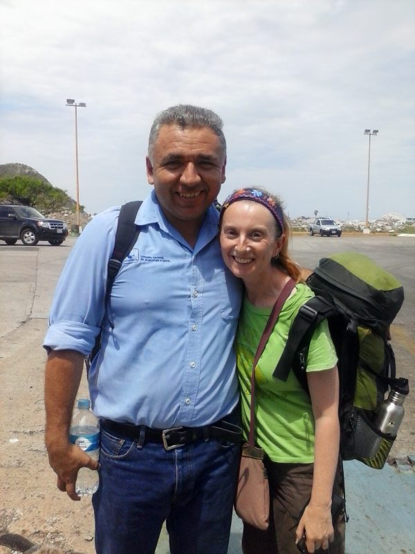 Man with blue shirt and woman with green shirt and backpack posing with smiles.