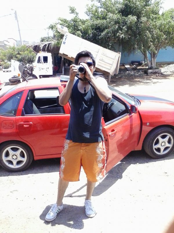 Man with camera in front of a red car.