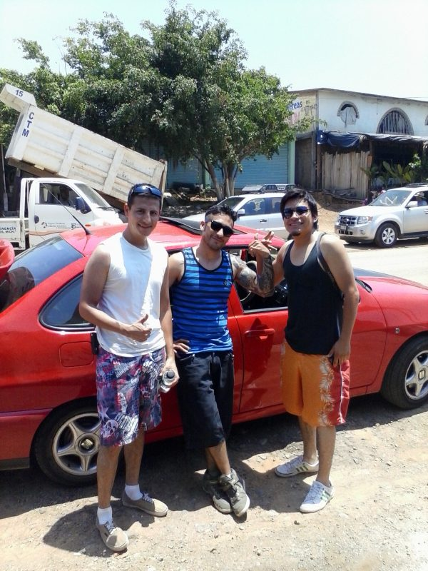 Three men in front of a red car.