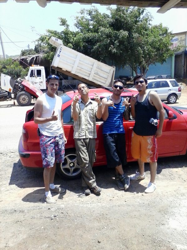Four men in front of a red car.