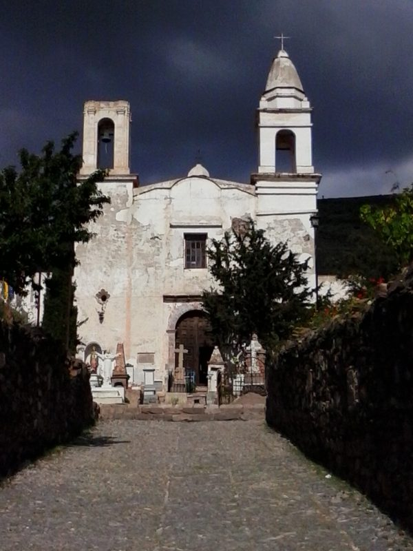 A white church agains the background of a very dark sky in the town of Real de Catorce in the state of San Luis Potosi in Mexico