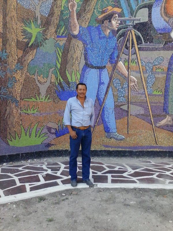 Man posing in front of a colorful mosaic.