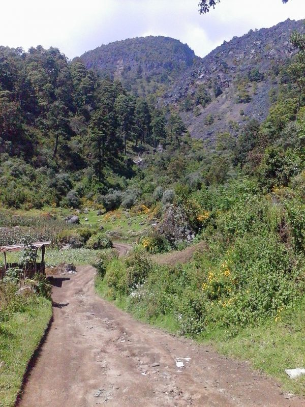 A dirt road running through lush mountains near Xela in Guatemala.
