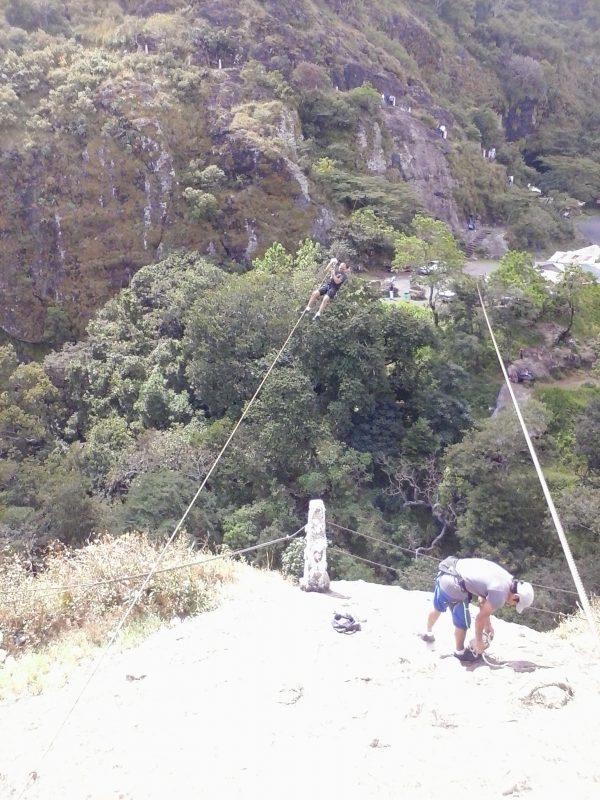 A man preparing a zip line at an overlook in San Salvador, El Salvador.