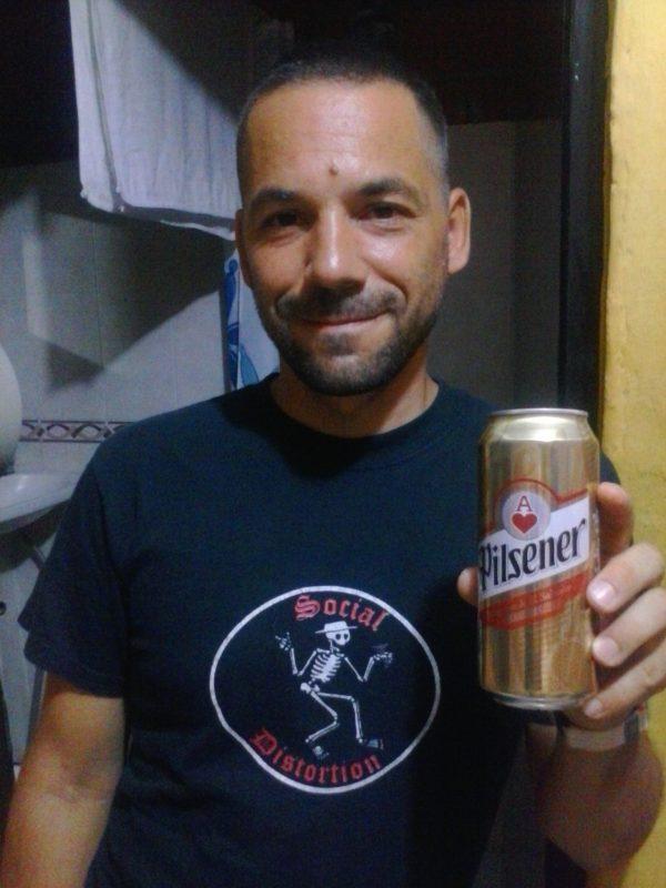 man in black shirt holding a gold can of Pilsner beer in El Salvador.