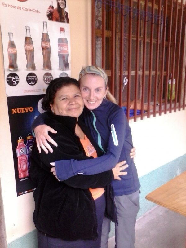 Two women hugging in front of a shop in Honduras.