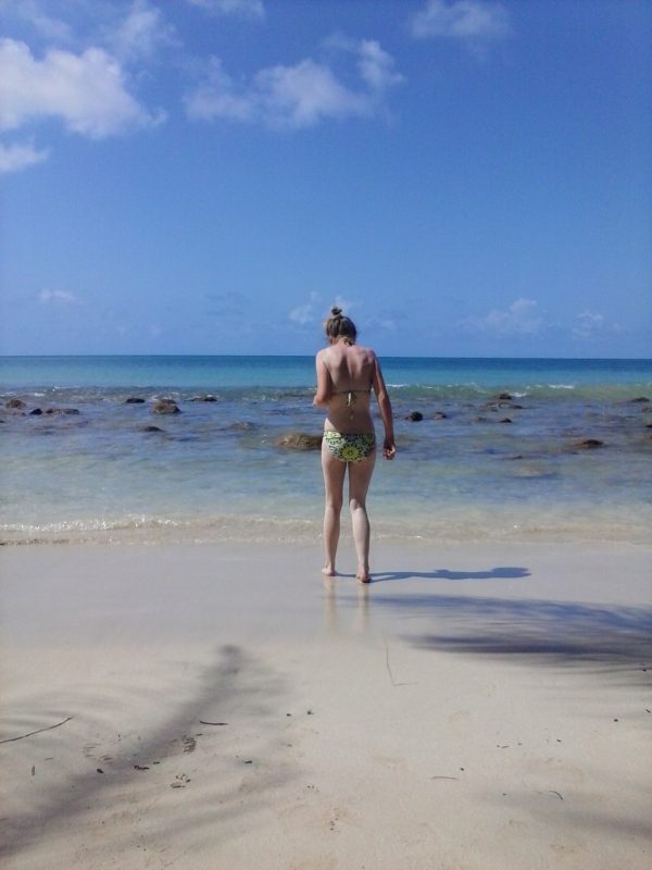 A woman walking into the water at a beach on Big Corn Island off the coast of Nicaragua.
