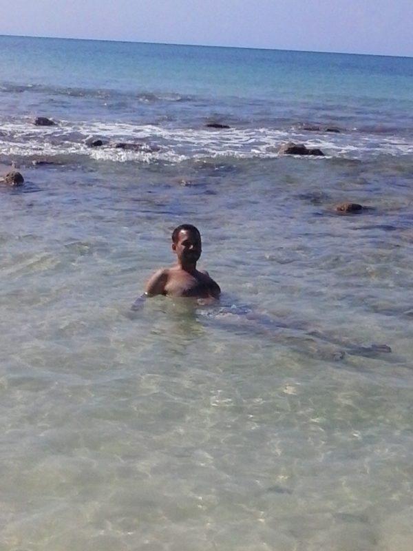 A man lying in shallow water on Big Corn Island off the coast of Nicaragua.