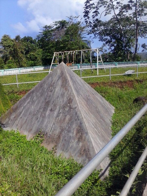 A concrete pyramid with a playground swing in the background.