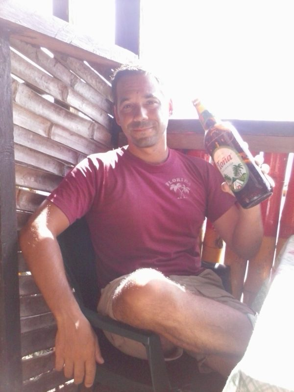 Man in burgundy shirt holding a bottle of Tona beer on Big Corn Island off the coast of Nicaragua.