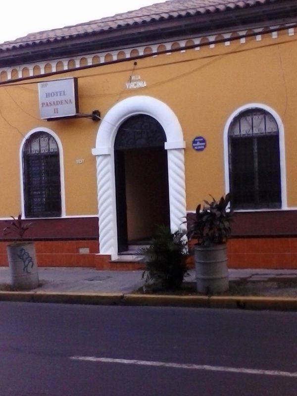 The front exterior entrance of the yellow-colored Hotel Pasadena II in San Salvador, El Salvador.