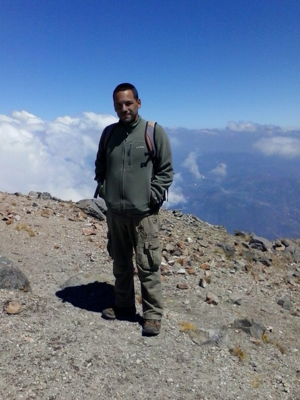 A man wearing a green fleece smiling after hiking Volcan Tajumulco.
