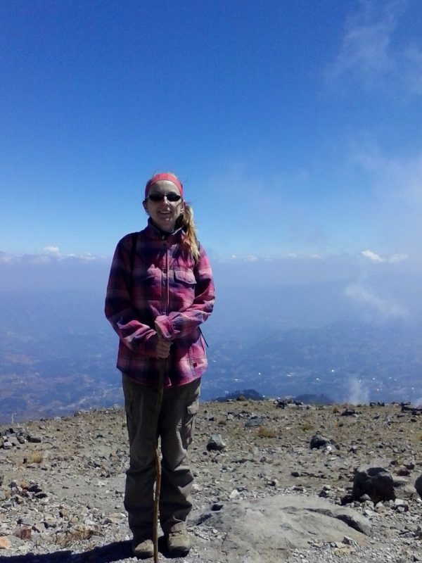 A woman wearing a pink flannel smiling after hiking Volcan Tajumulco.