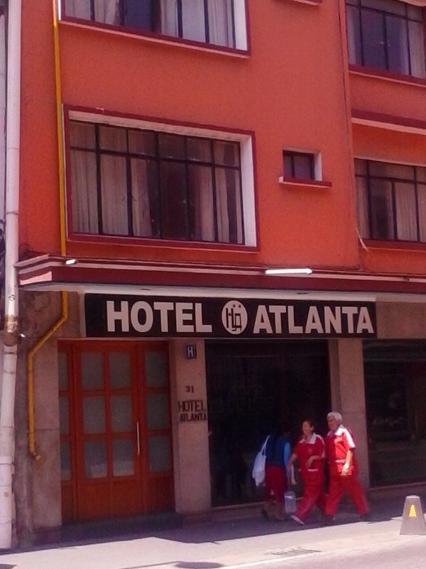 2 people in uniform walking in front of hotel atlanta in mexico city.