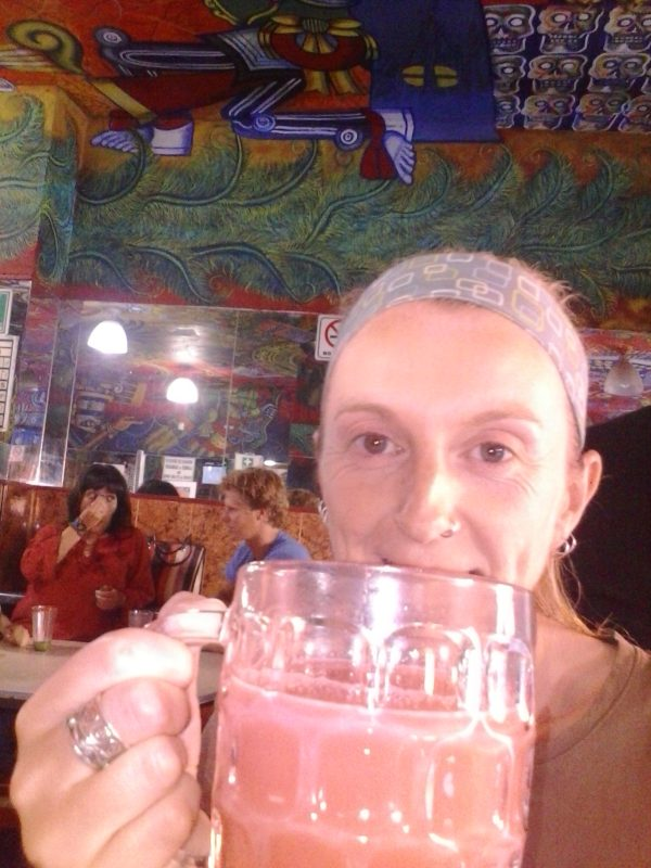 A woman drinking a mug of pink pulque.
