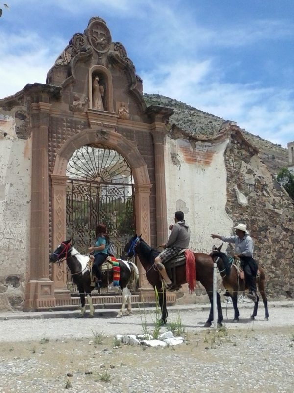 Three people on horseback in front of an old church gate in the town of real de Catorce in San Luis Potosi state in Mexico.