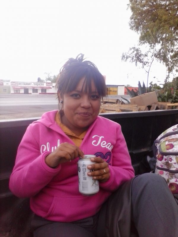 Woman in a pink pull-over drinking a can of beer.