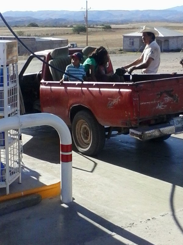 people in the back of a pick-up truck at a gas station.