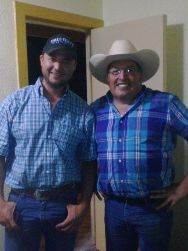 Two men in blue shirts posing for a photo.