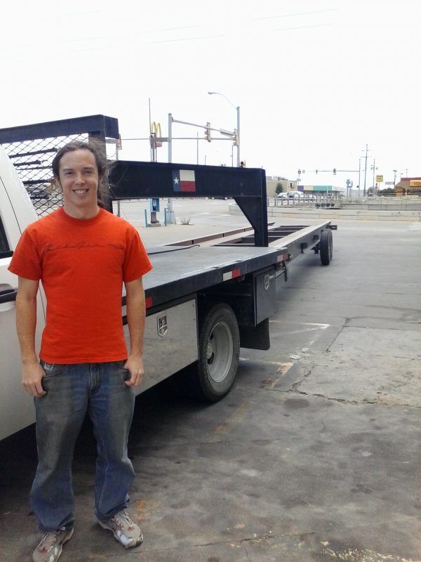 Man in orange shirt posing for a photo next to a trailer.