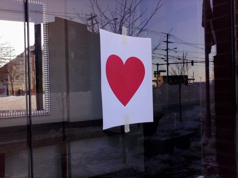 A red Valentine bandit heart taped to a window at a shop in Portland, Maine.