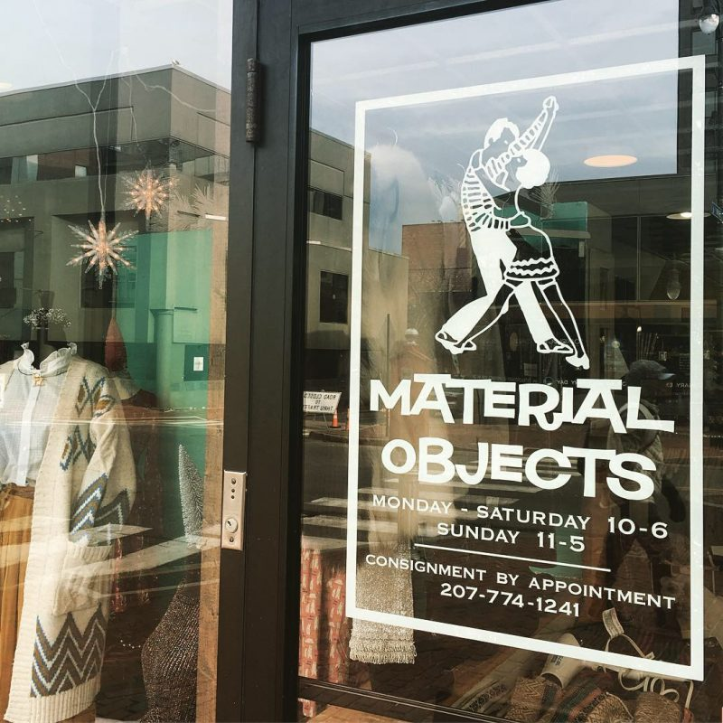 The glass-plated front door of the Material Objects clothing store in Portland, Maine.