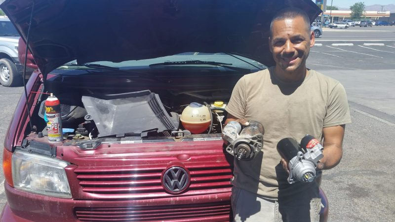 Man holding 2 starter motors in front of burgundy Volkswagen van with the hood up