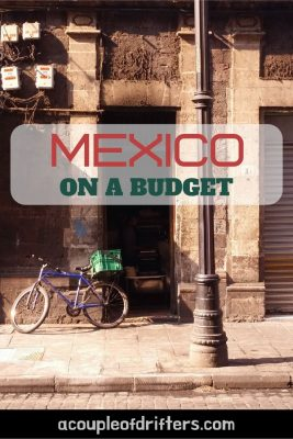 A blue bicycle with a green basket leaning against an old building advertising backpacking travel to Mexico on a budget.