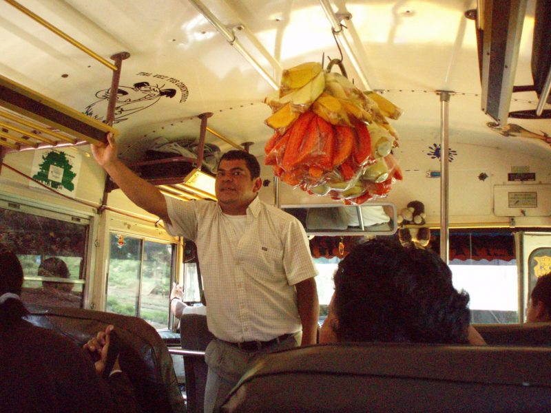 A man in a white shirt selling goods while standing in the front of a chicken bus in Guatemala.