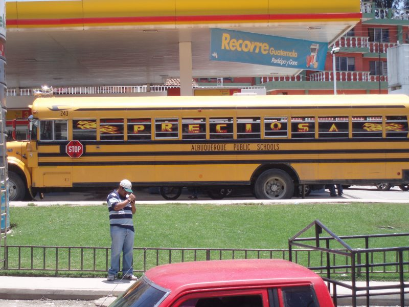 Man in baseball hat lighting a cigarette in front of a yellow school bus.