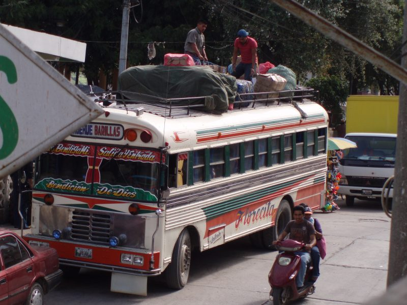 Two men tying down cargo on the top of a brightly-colored chicken bus in Guatemala.