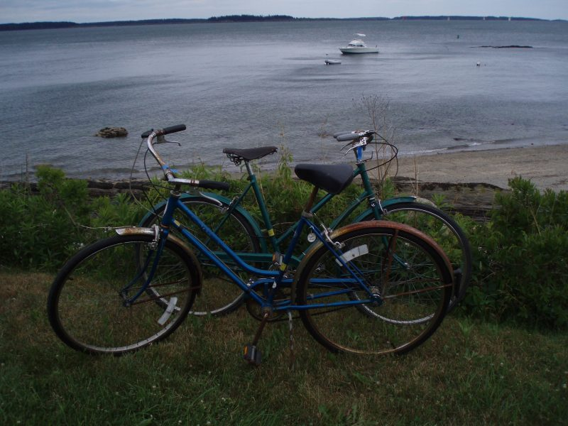 A view from Chebeague Island, Maine of two vintage bicycles with a lobster boat in the background.