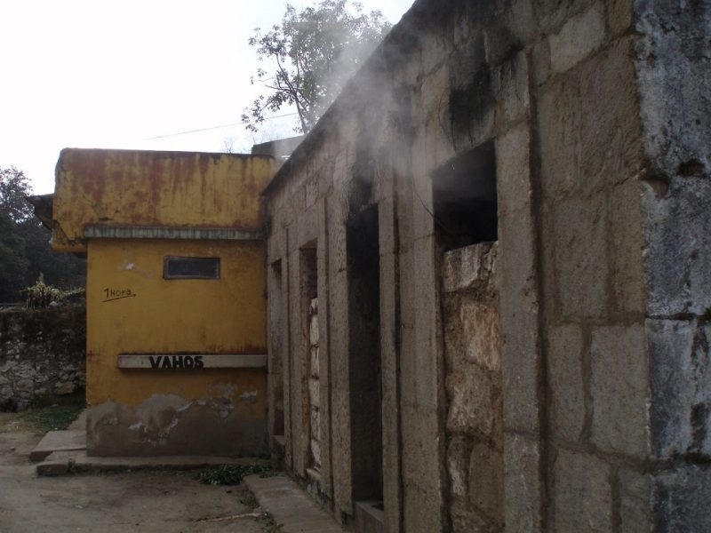 A concrete sauna building with steam coming out the widows and doors near Xela, Guatemala.