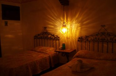 A dim light hanging between two twin beds in a hotel room in Mexico.