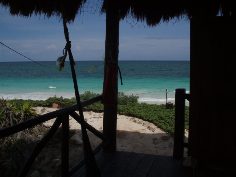 A porch with palapa roof with a light blue ocean in the background.