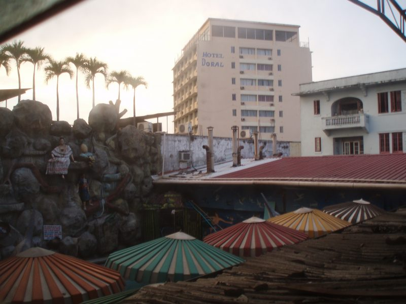 View of a large hotel building with several colorful parasols in the foreground.