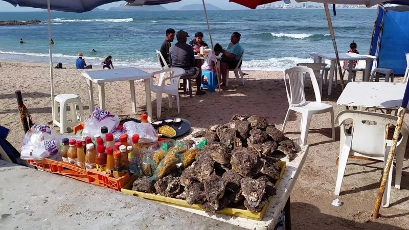 A family enjoying oysters at Playa Los Pinitos, located along the malecon in Mazatlan.