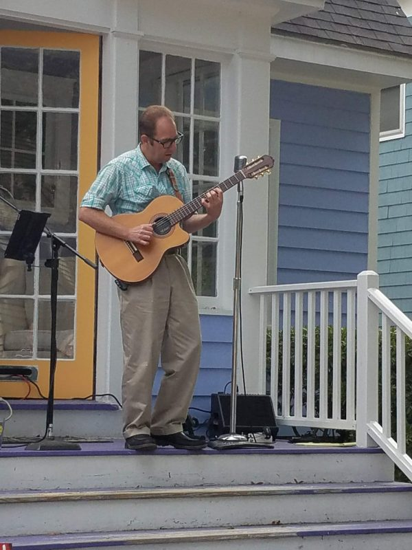 Sean Mencher playing an acoustic guitar on a porch in Portland, Maine.