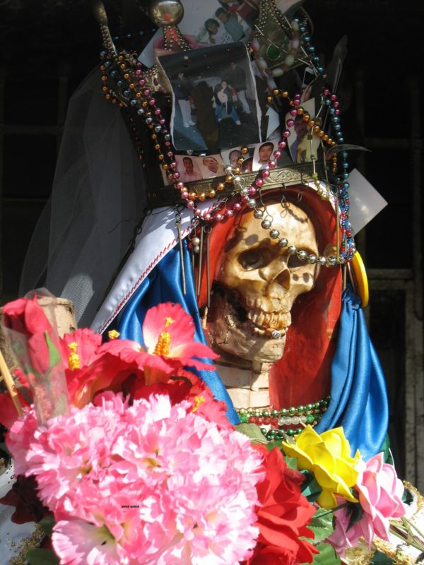 Skeleton wearing a crown strung with beads and wearing red and blue robes, holding a bouquet of pink flowers at a shrine in Mexico City.