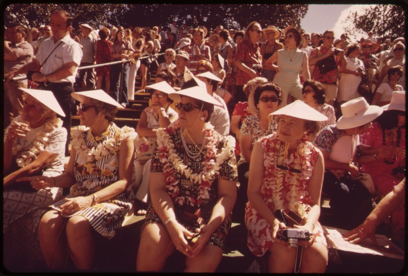 old photo of tourists wearing hats.
