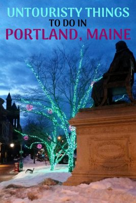 A silhouette of a seated statue and and some trees with Christmas lights at Longfellow Square in Portland, Maine.