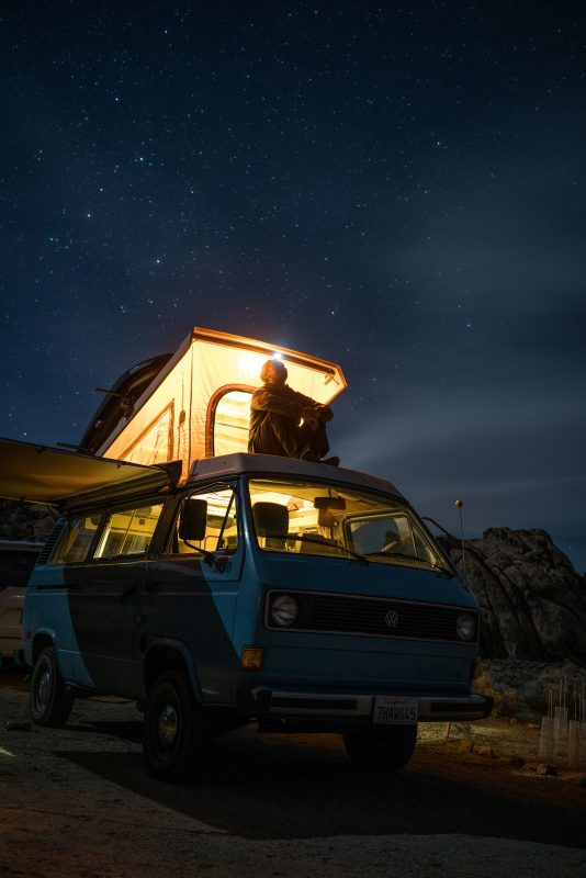 Man sitting on roof of van looking at stars.