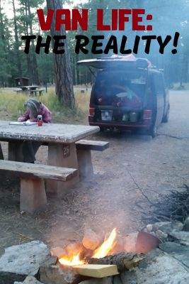 person writing at campfire with campervan.