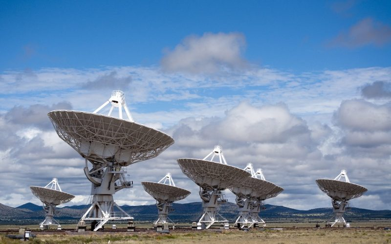 Several large radio telescopes pointing into the sky.