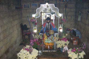 The likeness of San Simon in Zunil, Guatemala, wearing a sombrero and sunglasses, as is typical.