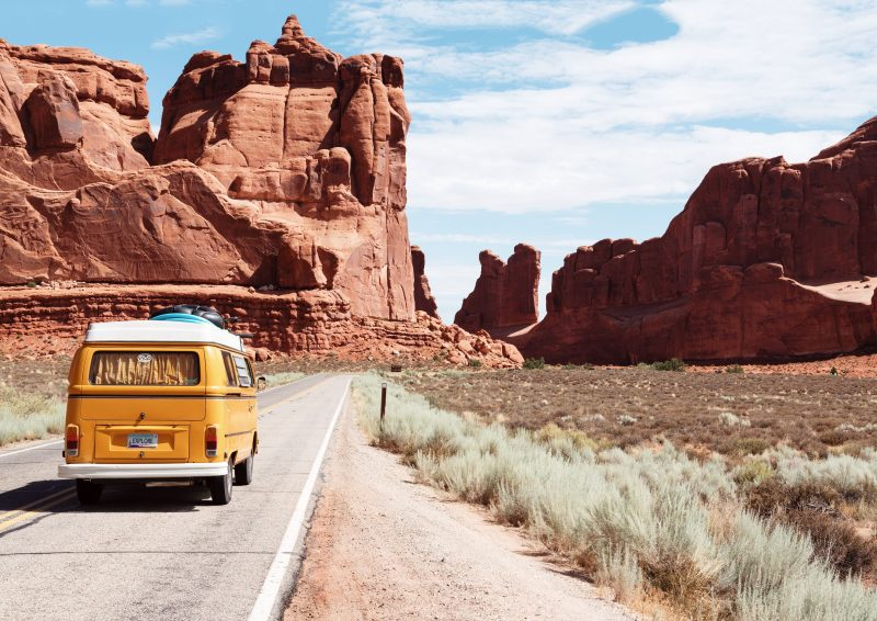 Yellow Volkswagen bus driving toward red rocks in the desert.