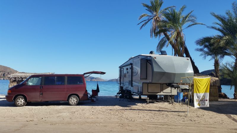 Volkswagen van and an RV baja camping on a white sand beach with a palm tree in the background