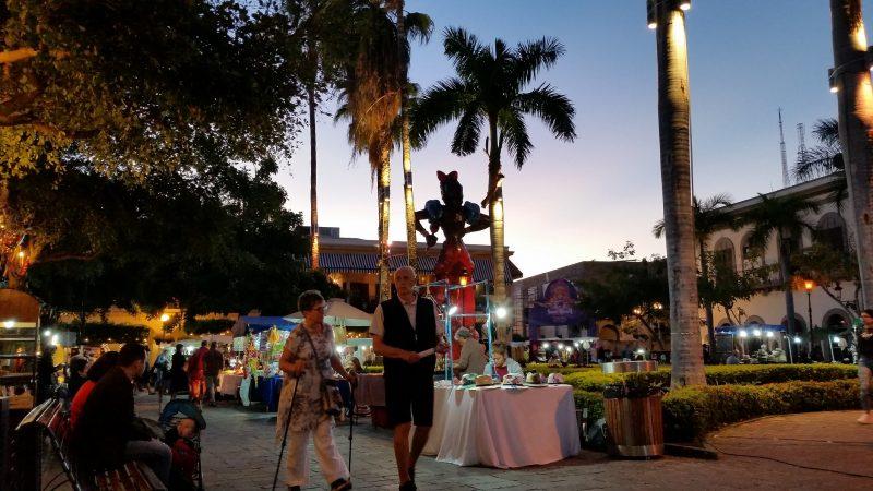Vendors and pedestrians in a square at dusk in Mazatlan.
