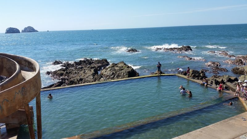 A ocean front infinity pool with several people swimming in it in Mazatlan, Mexico.