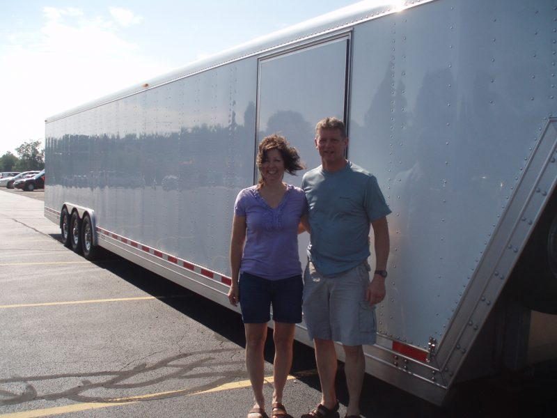 Man and woman standing in front of a trailer.